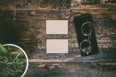 Mock-up of two blank craft business cards,glasses, smartphone and cactus on natural brown authentic wooden desk royalty free stock image