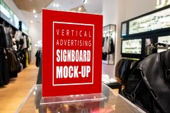 Mock up vertical advertising billboard at fashion clothing shop. Mock up perspective blank vertical advertising signboard in acrylic frame on showcase with stock photography