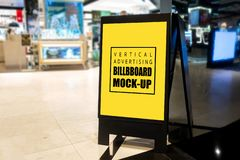Mock up vertical advertising billboard on floor. Mock up vertical blank billboard stand with clipping path to show promotion or discount, tall yellow screen stock images