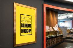Mock up vertical advertising billboard in gold frame. Mock up perspective the vertical blank billboard in golden frame on black wall at walkway front of showroom royalty free stock image
