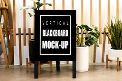 Mock up vertical advertising blackboard on floor at restaurant. Mock up perspective blank vertical blackboard with clipping path standing on floor at front of royalty free stock photography
