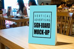 Mock up vertical advertising signboard on table in canteen. Mock up blank vertical advertising signboard in acrylic frame with clipping path on table in stock image
