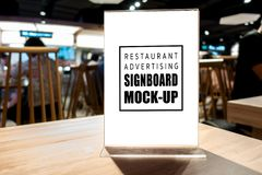 Mock up vertical advertising signboard on table in restaurant. Mock up blank vertical advertising signboard in acrylic frame with clipping path on table in stock photo