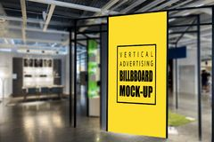Mock up vertical billboard in black frame. Mock up blank yellow screen of vertical billboard in black frame with clipping path at front of showroom in mall stock images