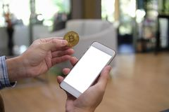 Mock up white color on screen cell phone and golden bitcoin in h Royalty Free Stock Photography