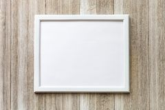 Mock up with white frame on a rustic wooden background with copy stock images