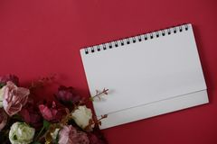 Mock-up white paper with space for text or picture on red background and flower royalty free stock images