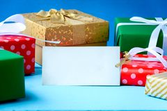 Mock up white text label and gift boxes on the wood table. With the holiday season Royalty Free Stock Photos