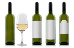 Mock-up of white wine bottles with blank white labels and a glass of wine stock photos