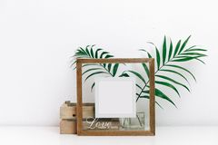 Mock up wooden frame with green tropical leaves. Nordic decorations,. Scandinavian interior royalty free stock image