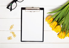 Mock up with yellow tulips, glasses and clips Royalty Free Stock Photo