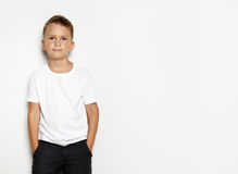 Mock up of young kid wearing black shorts. Mock up of young kid showing some action on the white background and wearing white shorts Stock Images