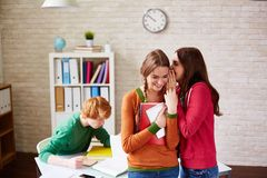 Mockery. Teenage girl whispering something to her friend with their groupmate behind Royalty Free Stock Image