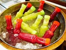 Mocktail ha mescolato il succo di frutta in bottiglie di plastica raffreddate nel carro armato con il freddo dell'acqua e del ghi immagine stock