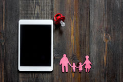 Mockup for adoption concept. Tablet PC near baby pacifier on dark wooden background top view copyspace Royalty Free Stock Photo