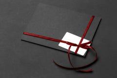 Mockup biała prezent karta na kartka z pozdrowieniami z czerwonym łękiem przy czernią Obraz Stock