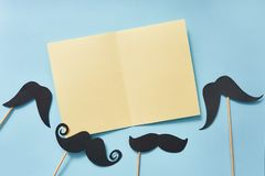 Mockup black mustaches on blue paper background top view. Happy fathers day greeting card with yellow sheet of paper and place for stock photos