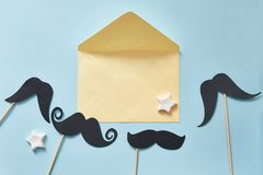 Mockup Black mustaches on blue paper background and yellow envelope. Happy fathers day greeting card with place for text. Hipsters stock photo
