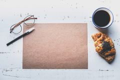 Mockup blank craft sheet of blank craft paper, pen, eye glasses and morning coffee cup with croissant on white wooden Royalty Free Stock Image