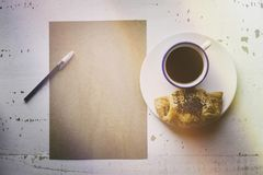 Mockup blank craft sheet of blank craft paper,pen, eye glasses and morning coffee cup with croissant on white wooden. Mockup blank craft sheet of blank craft Royalty Free Stock Images