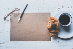 Mockup blank craft sheet of empty paper, pen, eye glasses and morning coffee cup with croissant on white wooden desk. Business background for letter writing Stock Image