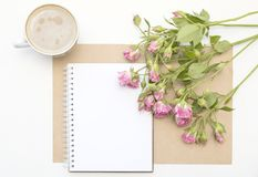 Mockup with blank notepad, cup of coffee and little garden pink roses. Morning still life. Stock Image