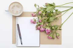 Mockup with blank notepad, cup of coffee and little garden pink roses. Morning still life. Stock Photos