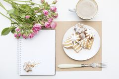 Mockup with blank notepad, cup of coffee and little garden pink roses. New year cookies and cappuccino. Christmas Royalty Free Stock Images