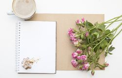 Mockup with blank notepad, cup of coffee and little garden pink roses. New year cookies and cappuccino. Christmas Stock Images