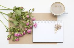 Mockup with blank notepad, cup of coffee and little garden pink roses. New year cookies and cappuccino. Christmas Stock Photos