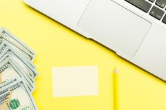 Mockup Blank page with laptop and cash money on yellow background. Top view with copy space for input the text. Flat lay, business
