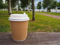 Mockup of brown paper takeaway coffee cup on wooden surface on summer park background, for product display montage. royalty free stock photo