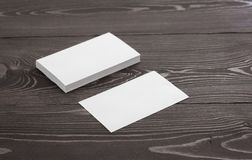 Mockup of business cards on a dark wood background. Template for branding identity stock photo