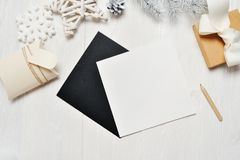 Mockup Christmas black greeting card letter in envelope and gift, flatlay on a white wooden background, with place for. Your text. Flat lay, top view photo mock stock image