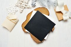 Mockup Christmas black greeting card letter in envelope and gift with white tree, flatlay on a white wooden background Stock Photos