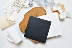 Mockup Christmas black greeting card letter in envelope and mug, flatlay on a white wooden background, with place for Stock Images