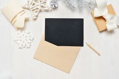 Mockup Christmas black greeting card letter in envelope and pencil, flatlay on a white wooden background, with place for Stock Photography