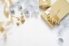 Mockup Christmas gift gold bow ribbon and tree cone, flatlay on a white wooden background, with place for your text Royalty Free Stock Images