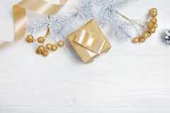 Mockup Christmas gift gold bow ribbon and tree cone, flatlay on a white wooden background, with place for your text Royalty Free Stock Photo