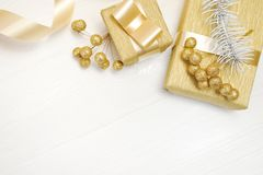 Mockup Christmas gift gold bow ribbon and tree cone, flatlay on a white wooden background, with place for your text Royalty Free Stock Photography