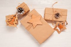 Mockup Christmas kraft gift boxes with xmas wooden toys on wooden background. Top view for greeting card with place for text.  royalty free stock image