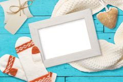 Mockup Christmas white frame with knitted mittens, flatlay on a white wooden background with a ribbon, with place for Royalty Free Stock Photo