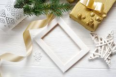 Mockup Christmas white frame with tree and golden ribbon and a gift, flatlay on a white wooden background, with place royalty free stock photo