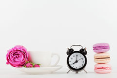 Mockup of coffee cup with rose flower, macaroon and alarm clock on white desk with clean space for text and design your blogging. Royalty Free Stock Photography