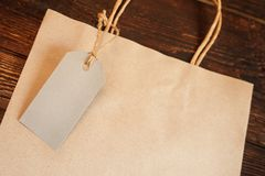 Mockup craft paper shopping bag with tag on vintage wooden table background. Top view Stock Image