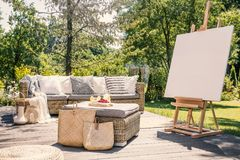 Mockup of easel on wooden terrace with rattan table and settee in the garden. Real photo Royalty Free Stock Images
