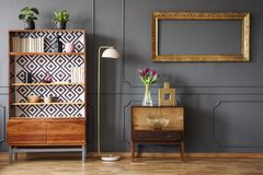 Mockup of empty gold frame above cabinet in grey retro living room interior with lamp. Real photo royalty free stock images
