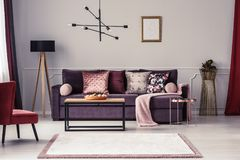 Woman`s living room interior. Mockup of empty poster above violet sofa with pink blanket in woman`s living room interior royalty free stock images