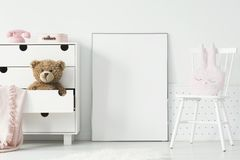 Mockup of empty poster between cabinet with teddy bear and white stock photography