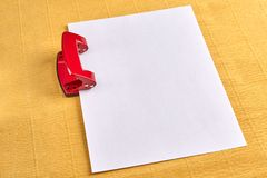 Red hole puncher with empty sheet of paper, yellow background. Royalty Free Stock Images